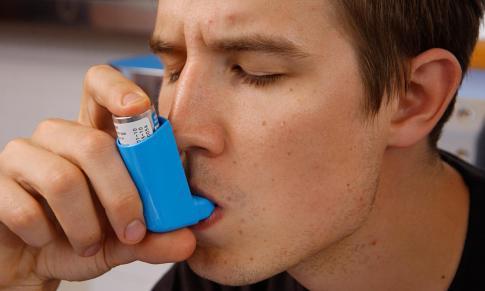 Man using an inhaler for asthma