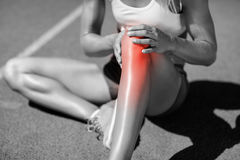 low-section-female-athlete-suffering-joint-pain-sitting-track-sunny-day-93245433